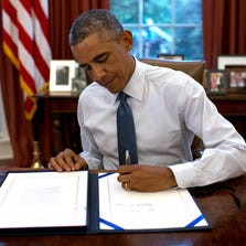 WASHINGTON, DC - SEPTEMBER 19:  U.S. President Barack Obama signs H.J.Res. 124 Continuing Appropriations Resolution in the Oval Office of the White House September 19, 2014 in Washington, DC. The continuing resolution funds the federal government through December 11, 2014.  (Photo by Win McNamee/Getty Images)