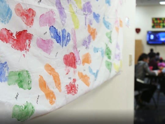 A canvas of painted footprints hands at the Freehold