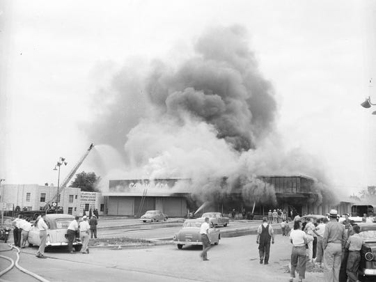 Firefighters work to put out the fire at Consumers Warehouse. A firework explosion set the blaze that killed three people. Fifteen employees and a few customers were able to escape the fire, but the building was declared a total loss. Similar photograph published in the Leader & Press on June 29, 1955.
