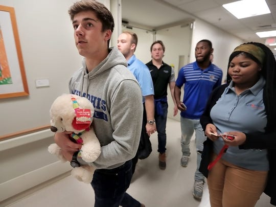 Memphis football player Riley Patterson (left) leads his teammates to visit Le Bonheur Children's Hospital patients last year.