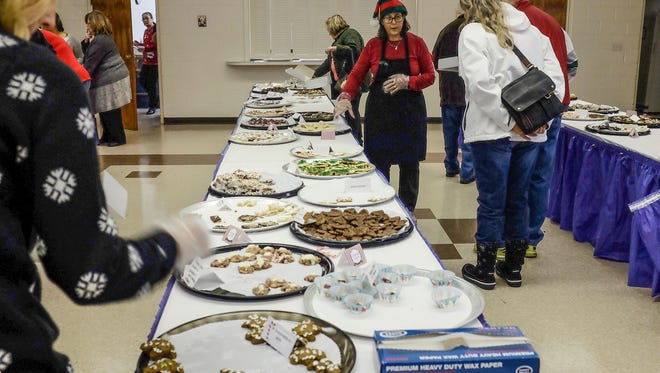 People browse and select the quickly disappearing cookies at the annual Cookie Walk fundraiser at St. Andrew Orthodox Church in East Lansing Saturday, December 10, 2016.