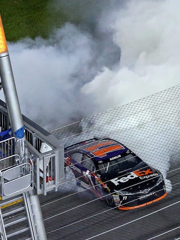 Denny Hamlin smokes up the frontstretch as he celebrates