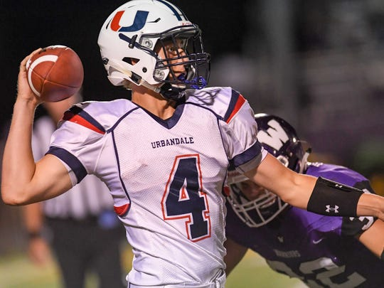 Urbandale Quarterback Luke Llewellyn (4) scrambles as Waukee's Jake Morrison (32) moves in for the sack on Friday, Aug. 25, 2017, during a football game between Waukee and Urbandale High School.