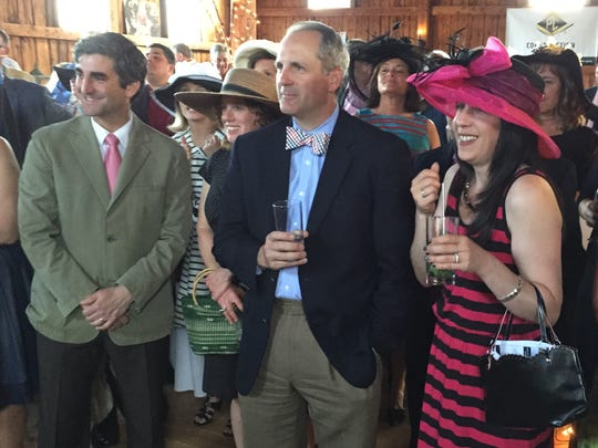 Burlington Mayor Miro Weinberger, left, Jeff McMahn of Burlington and  Anna Syrell of Bristol watch the race during the Kentucky Derby Gala on Saturday.