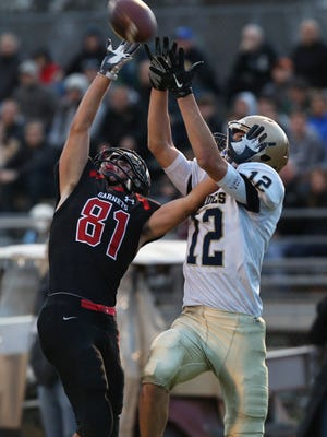 Lourdes' Luke Timm (12) intercepts a pass intended for Rye's Brett Egan (81) during the Section 1 Class A championship football game at Arlington High School on Saturday.