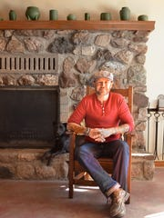 Clay Cross poses in front of the fireplace at the Morongo Valley home he shares with his life partner. They bought their home about three years ago, fixed it up, and Cross began the challenging process of finding full-time work. He starts a new job in December that values his professional experience in health care and fully accepts his gender identity as a transgender man.