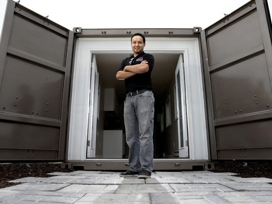Josh Atencio, a 3-D architectural designer for MODS International, stands in front of a repurposed shipping container that can function as temporary housing for disaster relief, a hunting lodge or a small home. The unit is on display at the company's headquarters in Grand Chute.