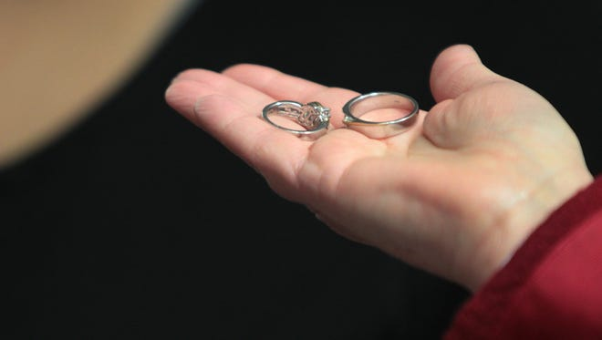 Marion County Clerk Beth White holds wedding rings as she marries a couple at the City County Building on Valentine's Day, Feb. 14, 2014.