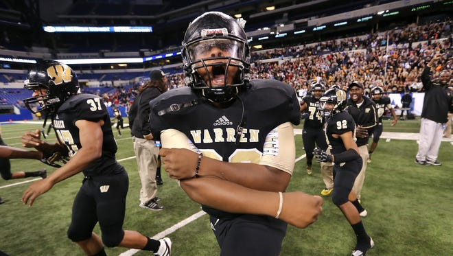 Warren Central player Davonte Guthrie and his teammates rush the field in celebration after beating Carmel in the IHSAA Class 6A State Football Finals held at Lucas Oil Stadium on Saturday, November 30, 2013. Warren Central beat Carmel 7-6.