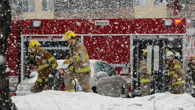 Waite Park firefighters carry a fan through heavy snowfall into an apartment building on Seventh Street South in Waite Park Thursday afternoon.