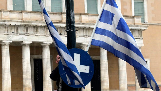 A worker places Greek flags in front of the Greek Parliament in Athens.