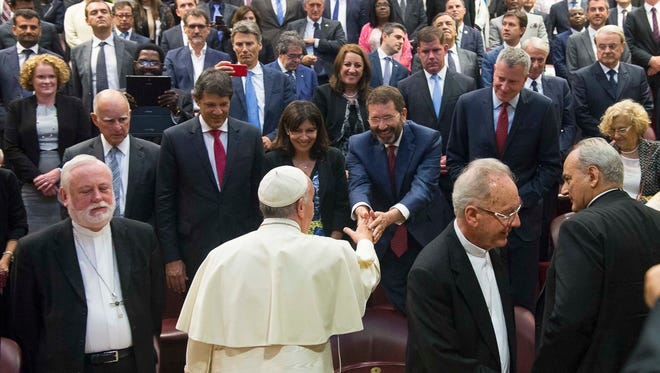 Pope Francis greets mayors from around the world at a conference on climate change and human trafficking held at the Vatican in July 2015.