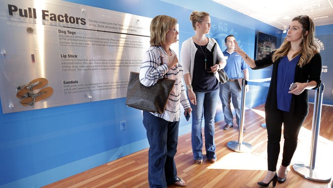 Esther Goetsch, right, of Truckers Against Trafficking, gives Vicki Johnson, left, and Julie Story, center, of Bowlin Travel Centers, a tour of an informational exhibit inside a trailer Thursday. The organization is asking truckers to keep an eye out for trafficked individuals who are often forced to work as prostitutes at truck stops.