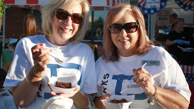 L-R Realtors from Parks Realty  Jayne Coleman and Marie Drahus sample some ribs from Texas Roadhouse at A Taste of Hendersonville on Thurs. Sept. 28, 2017.