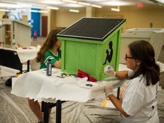 Alida Lewis paints a Little Free Library during a Make