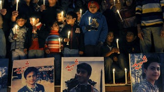 People light candles around pictures of some of those killed in an attack on an army run Peshawar school, Islamabad.