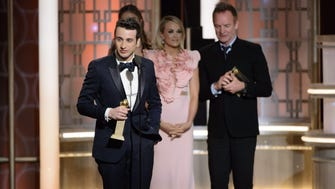 Justin Hurwitz (left) accepts the Golden Globe Award for Best Original Score - Motion Picture for 'La La Land' during the 74th annual Golden Globe Awards ceremony at the Beverly Hilton Hotel in Beverly Hills, California.