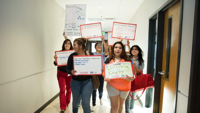 """Las Cruces High School ENLACE Teacher Sylvia Bustillos, rear left, walk down a hall inside Las Cruces High School on Thursday, October 6, 2016, with some of her students Berenis Huerta, 17, front left, Leann Roberson, 17, and Guendi Castro, 17, during a """"Walk In"""" to show support for schools during budget cuts."""