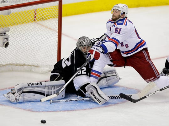 Los Angeles Kings goalie Jonathan Quick, left, blocks a shot by New York Rangers left wing Rick Nash during overtime in Game 2 in the NHL hockey Stanley Cup Finals in Los Angeles, Saturday, June 7, 2014. (AP Photo/Jae C. Hong)