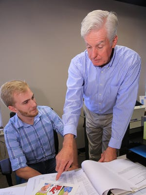Neal Udsen, left, discusses a marketing piece with Jerry Lynch.