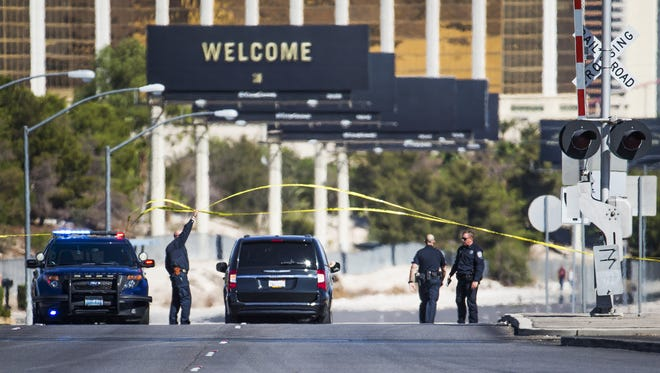 Police allow a vehicle to pass a roadblock on Las Vegas Blvd. near Mandalay Bay Monday morning, October 2, 2017. At least 58 people were shot to death at a country music concert near Mandalay Bay, Sunday evening, Oct. 1, 2017.