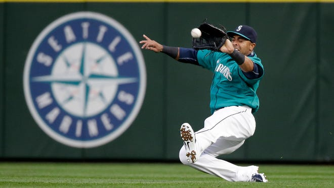 Seattle Mariners right fielder Nelson Cruz slides in to snag a fly ball from Minnesota Twins' Torii Hunter during the fourth inning of a baseball game Friday, April 24, 2015, in Seattle.