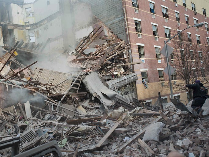 Emergency personnel work at the scene of an explosion and building collapse on March 12 in the East Harlem neighborhood of New York City.