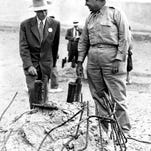 Gen. Leslie R. Groves, right, and Dr. J. Robert Oppenheimer, who cooperated on the development of the atomic bomb, survey the area in Alamogordo, New Mexico, where a tower once stood before the test bomb exploded.
