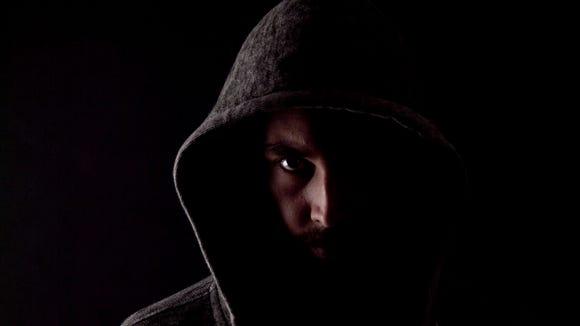 A man wearing a dark hoodie.