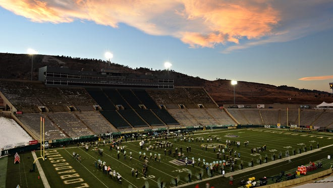 The sun sets over Hughes Stadium as the CSU marching band practices on Saturday prior to the venue's final game.