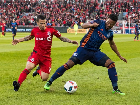 Toronto FC's Sebastian Giovinco, left, battles for the ball with New York City FC's Ethan White during the first half of an MLS soccer game against New York City FC on Wednesday, May 18, 2016, in Toronto. (Mark Blinch/The Canadian Press via AP)