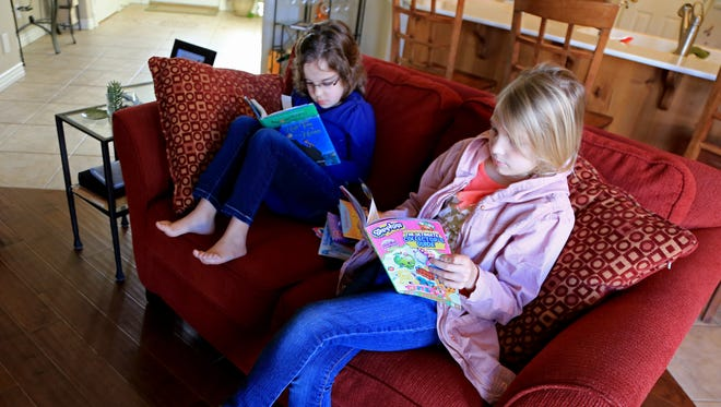 Olivia MacKay and Audrey Miller read books at Olivia's home in St. George. Both girls have dyslexia and have benefited from private tutoring.