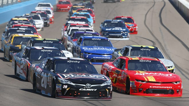 Erik Jones (20) and Justin Allgaier (7) lead the field after a restart during the DC Solar 200 at Phoenix International Raceway on March 18, 2017 in Avondale, Ariz.