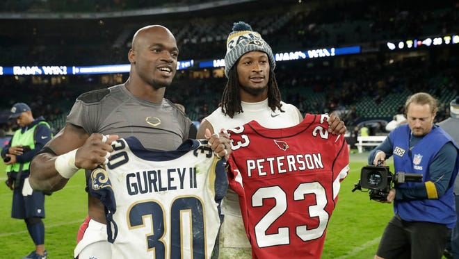 Los Angeles Rams running back Todd Gurley (30), right, exchanges shirts with Arizona Cardinals running back Adrian Peterson (23) after an NFL football game at Twickenham Stadium in London, Sunday Oct. 22, 2017. The Rams won the match 33-0.
