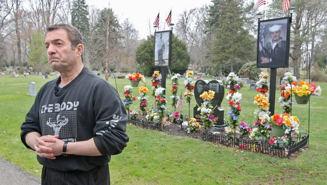 This photo taken on Wednesday, April 23, 2014, shows Fred Molai at the gravesite of his son, Adam, at Standing Rock Cemetery in Kent, Ohio.