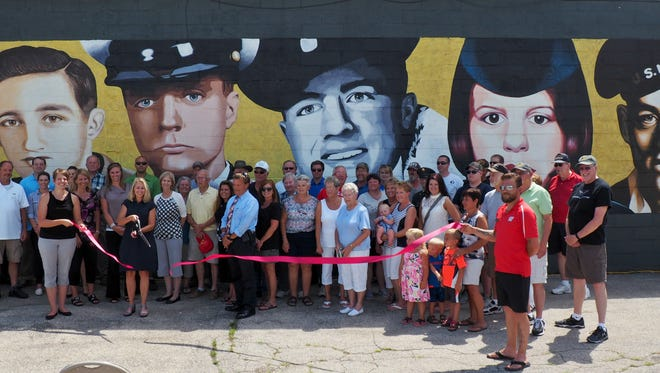 Veterans, their families, members of Leadership Fond du Lac and local dignitaries posed before the new mural while the ribbon was cut.