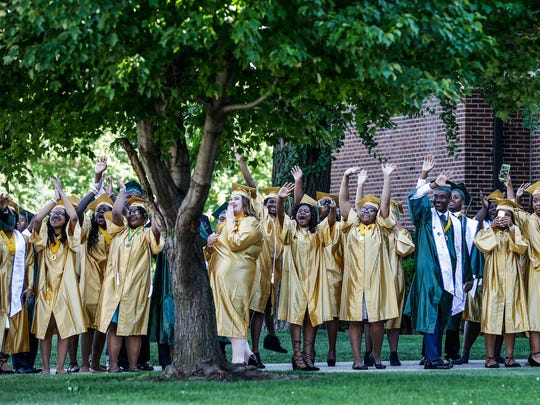 Crispus Attucks students wave hello and make noise for those who are across the street in the parking lot of New Baptist Church on Thursday, June 8, 2017. Those students barred from their graduation held a makeshift ceremony at the church.