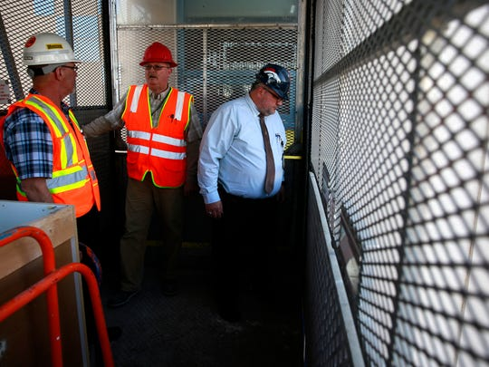 Larry Smith, director of facilities at San Juan Regional Medical Center, left, Pat Farrell of B & M Cillessen Construction Co., center, and Doug Frary, vice president of support services at SJRMC, ride in a construction elevator temporarily affixed to the exterior of the hospital on Feb. 10 in Farmington.