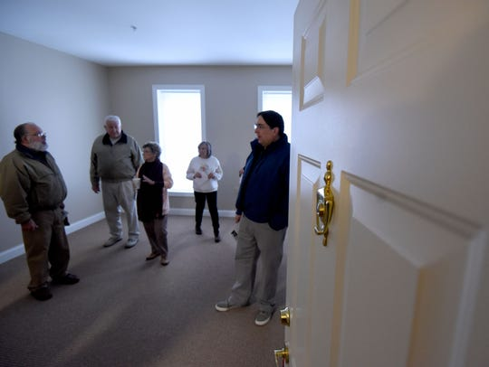 Visitors tour a one bedroom apartment at the Central