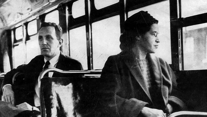 Rosa Parks sits in the front of a city bus in Montgomery in 1956, the day a Supreme Court ruling banning segregation of city public transit vehicles went into effect. A year earlier, Parks had been arrested for not giving up her bus seat.