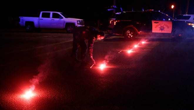 A police officer lights up flares near the scene where a shootout took place, in San Bernardino, Calif.