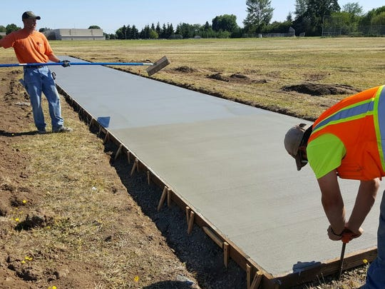 The concrete slab for a cricket pitch at Stephens-Yoshikai School Park is poured on July 13, 2016.