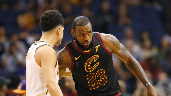 Phoenix Suns guard Devin Booker talks with Cleveland Cavaliers forward LeBron James before their game at University of Phoenix Stadium in Phoenix, Ariz. March 13, 2018.
