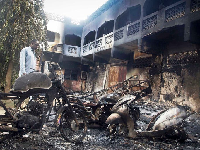 A man views destroyed vehicles and buildings after an attack by extremists on June 16 in Mpeketoni, Kenya. Forty-eight people were killed when Somali extremists attacked the small coastal town, assaulting the police station, setting two hotels on fire and gunning down local residents.