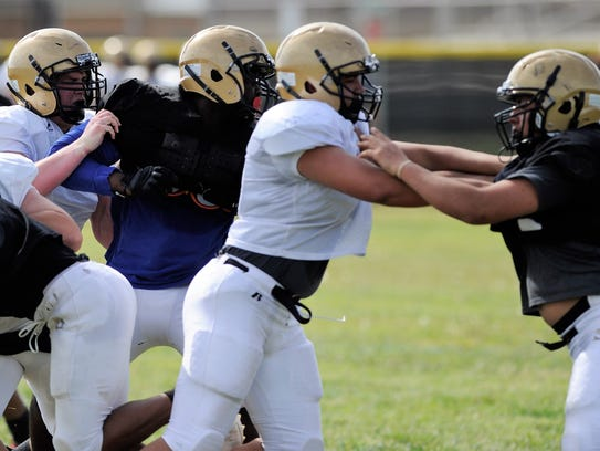 The Abilene High offensive and defensive lines battle during a drill Monday at the Eagles' first spring football practice.