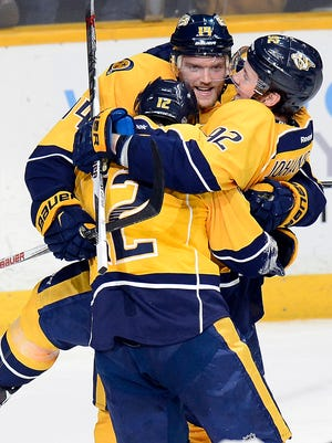 Predators center Mike Fisher (12) celebrates with defenseman Mattias Ekholm (14) and center Ryan Johansen (92) after Fisher scored a goal against the Los Angeles Kings during the second period.