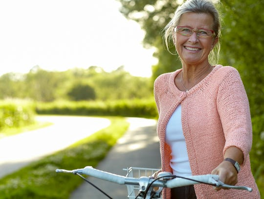 Smiling senior woman standing on a country lane with