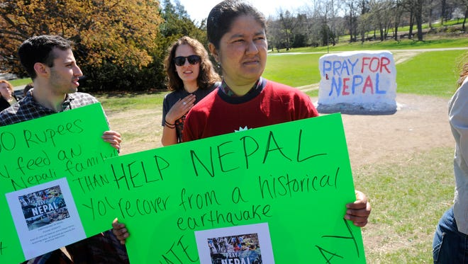 MSU student Hima Rawal takes part near  the rock on MSU's campus  in East Lansing Tuesday  during a fund raising effort for victiims of the Nepal earthquake.  Rawal is the president of the Nepalese Student Association at MSU.