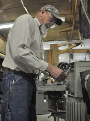 Standing over a belt sander, Mike Treadway smooths out the rough edges on a block of wood.