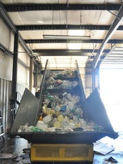 Plastic containers climb up a conveyor belt system before they're compacted and bundled.
